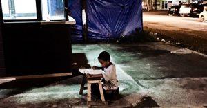 Bambino non ha la corrente elettrica e studia sul marciapiede